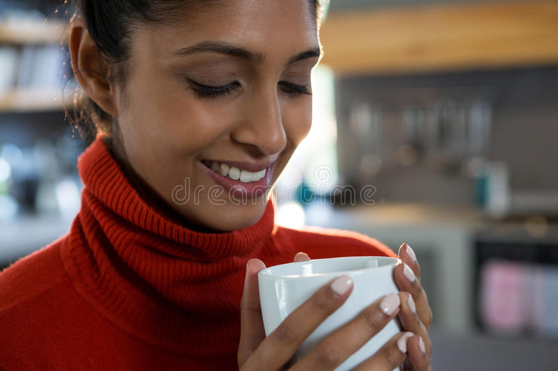 Smiling young woman having coffee stock photo