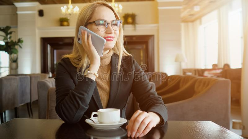 Smiling young woman having friendly phone conversation while drinking coffee in cafe stock images