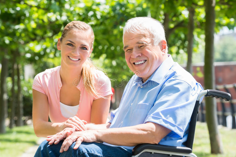 Smiling Young Woman With Her Disabled Father. Portrait Of A Smiling Young Woman With Her Disabled Father On Wheelchair royalty free stock image