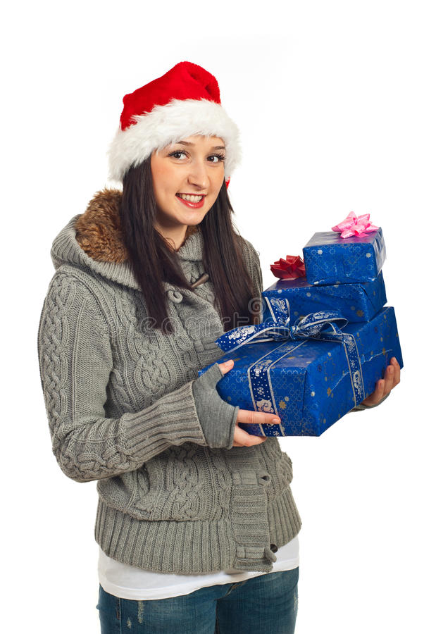Smiling young woman holding blue gifts. Smiling young woman with Santa hat holding blue Christmas gifts isolated on white background royalty free stock photos