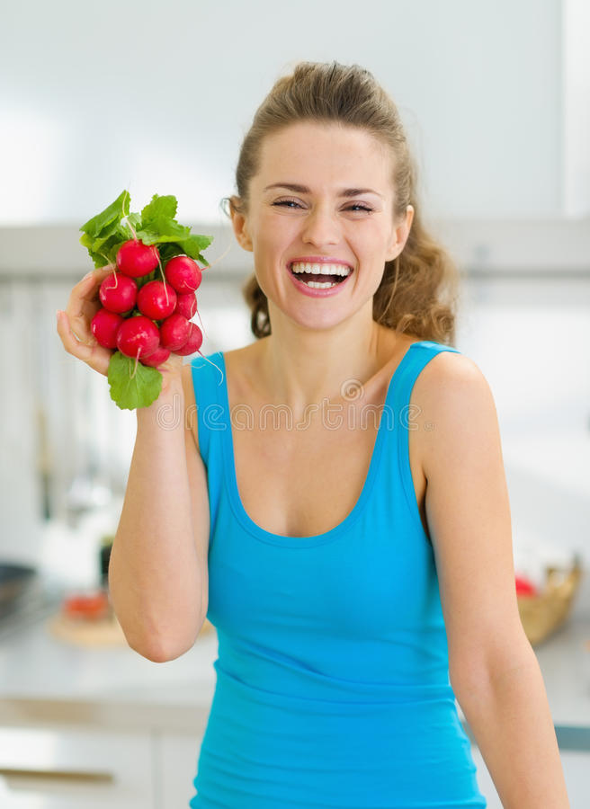 Smiling young woman holding bunch of radishes royalty free stock images