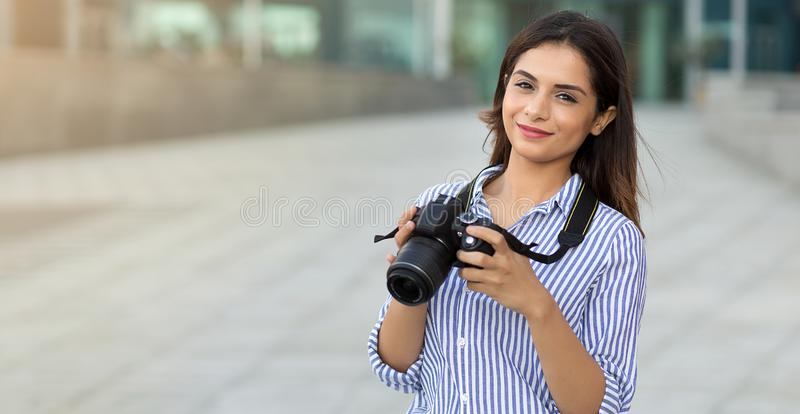 Smiling young woman holding the camera outdoors with copy space. Photographer, tourist royalty free stock photo