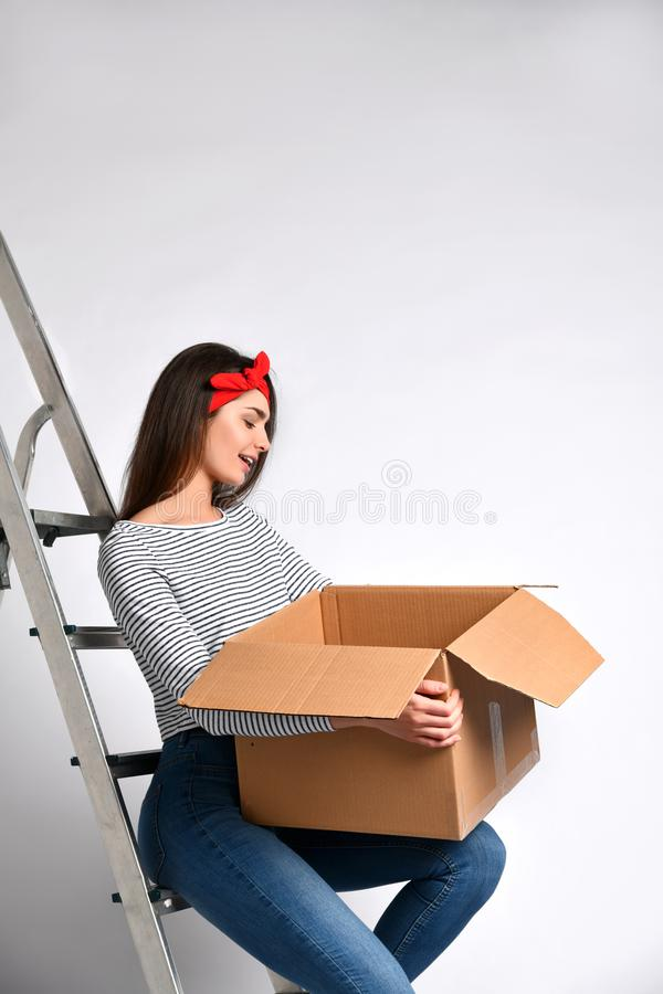 Smiling young woman holding cardboard box  on white background stock photography