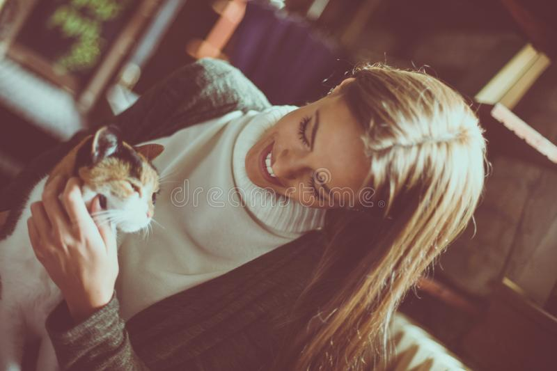 Smiling young woman holding cats pet in arms. From above stock image