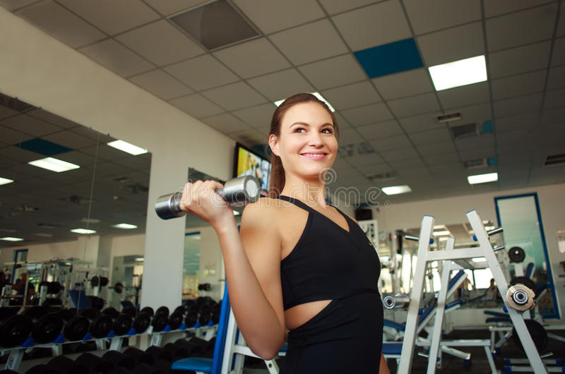 Smiling young woman holding dumbbells in gym royalty free stock photo