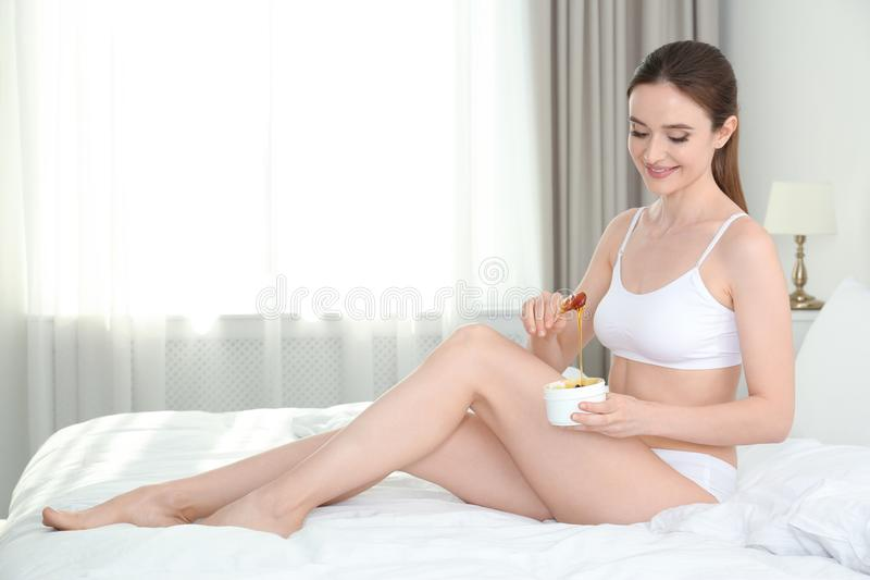 Smiling young woman holding hot wax for epilation procedure on bed at home. Space for stock photo