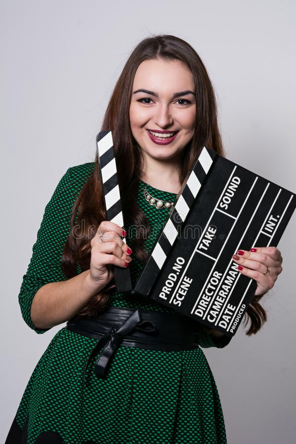 Smiling young woman holding a movie clapper. Cheerful girl in green dress helps in shooting a movie royalty free stock photo