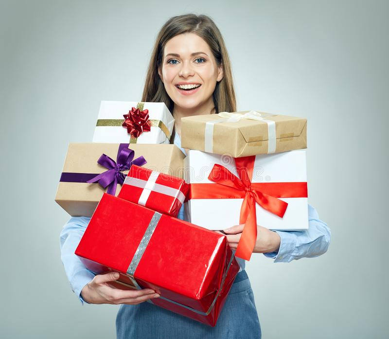 Smiling young woman holding pile of gifts. royalty free stock photos