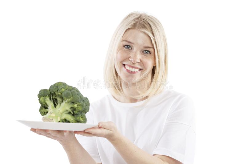 Smiling young woman holding a plate of broccoli in her hands. Vegetarianism and raw food diet. Health and proper nutrition. Isolated on a white background royalty free stock photo