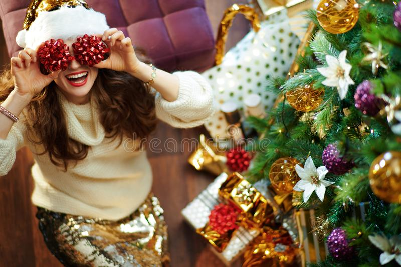 Smiling young woman holding red bows in front of eyes stock photography