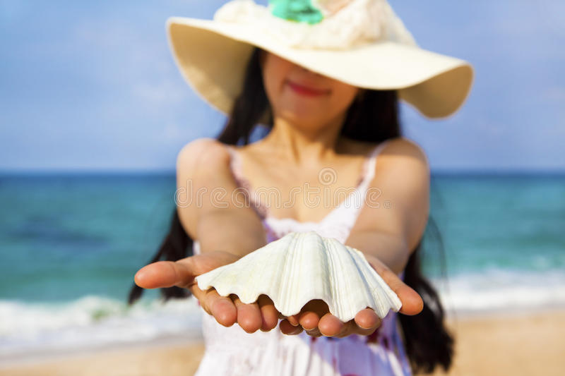 Smiling young woman holding shell