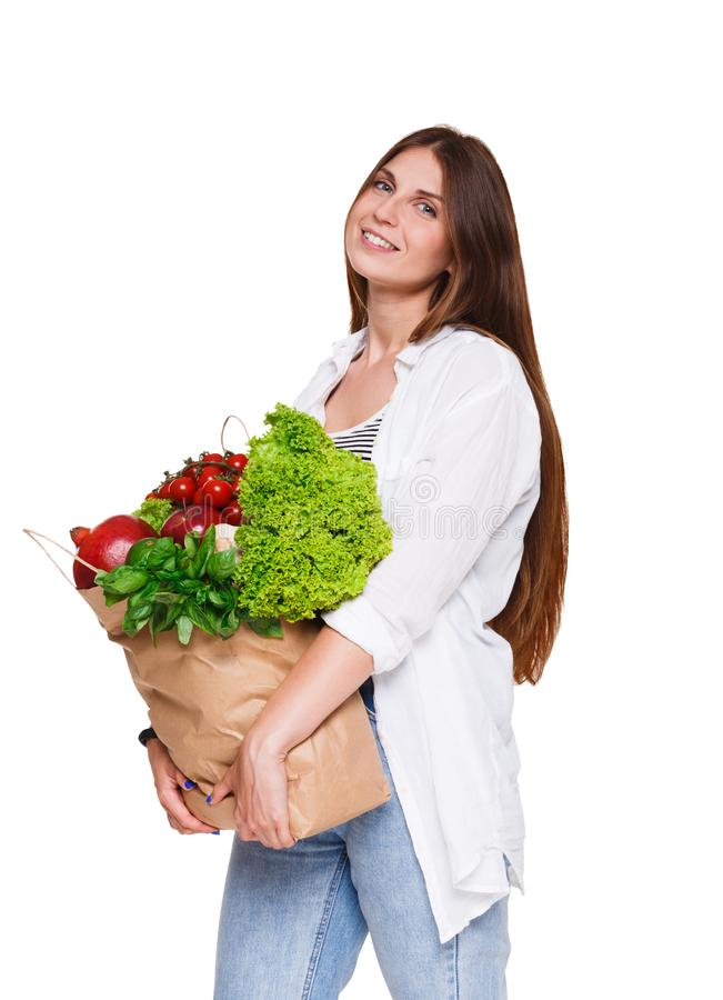Smiling young woman holding shopping bag full of vegetables isolated on white background. royalty free stock image