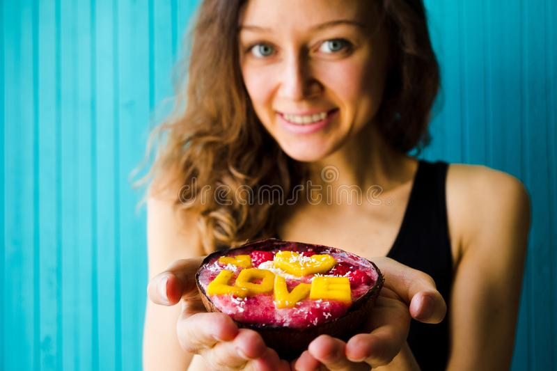Smiling young woman holding a smoothie bowl on a turquoise wooden background, copy space. The concept of proper stock photos