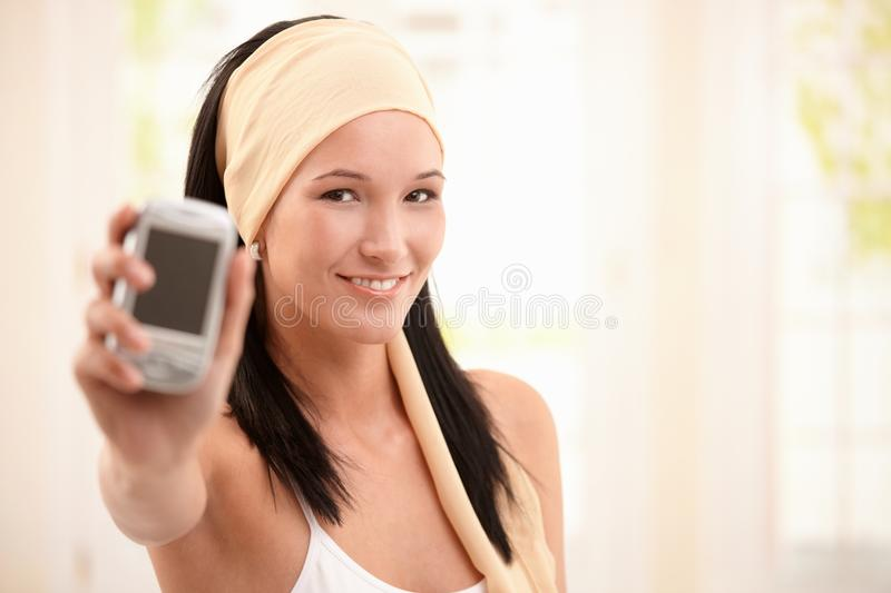 Download Smiling Young Woman Holding Up Mobile Phone Stock Photo - Image: 16761712