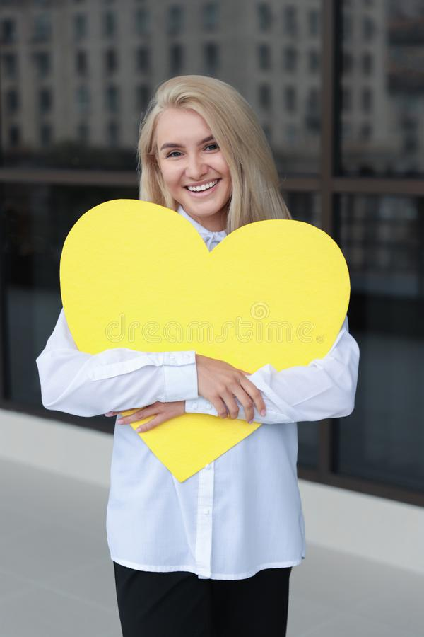 Smiling young woman holding a yellow plate in the hands royalty free stock images