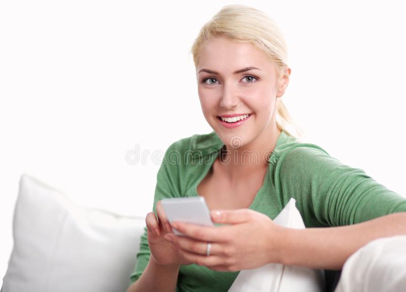 Smiling young woman at home relaxing on the couch, she is using a smartphone and texting royalty free stock image
