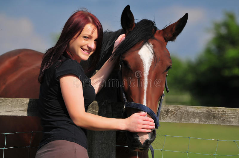 Smiling young woman with a horse. Young woman with a horse out in the field royalty free stock image