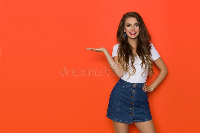 Smiling Young Woman In Jeans Mini Skirt And White Top Is Holding Hand Raised And Presenting. Smiling young woman in jeans mini skirt and white top is looking at royalty free stock image