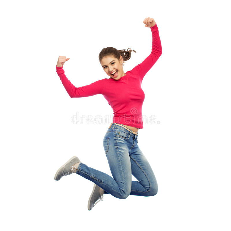 Smiling young woman jumping in air. Happiness, freedom, power, motion and people concept - smiling young woman jumping in air with raised fists over white stock photo