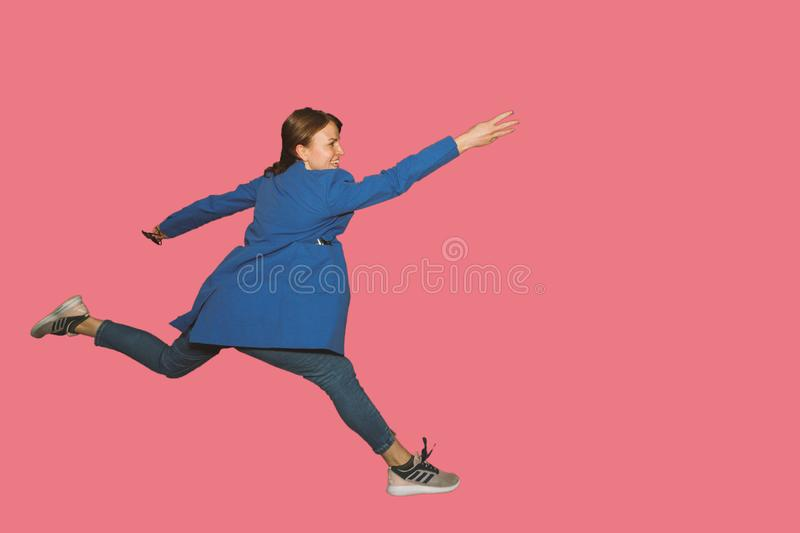 smiling young woman jumping in air with raised arms over pink background stock images