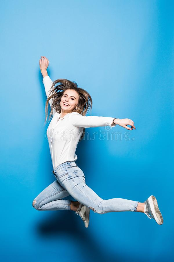 Happiness, freedom, power, motion and people concept - smiling young woman jumping in air with raised fists over blue background. Smiling young woman jumping in stock photography
