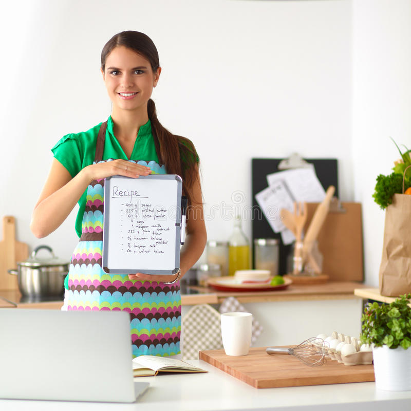 Smiling young woman in the kitchen, isolated on background. Smiling woman in the kitchen, isolated on background stock images