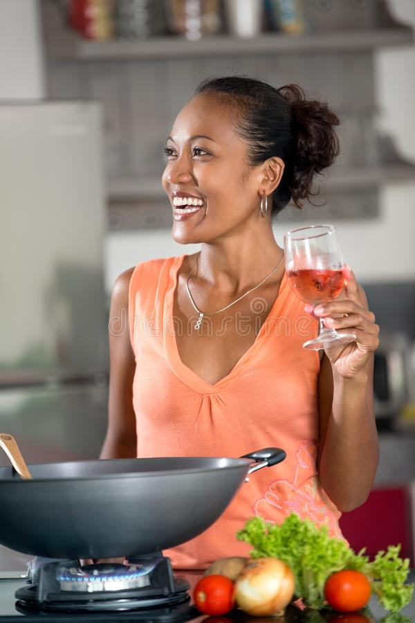 Smiling young woman in kitchen royalty free stock photography