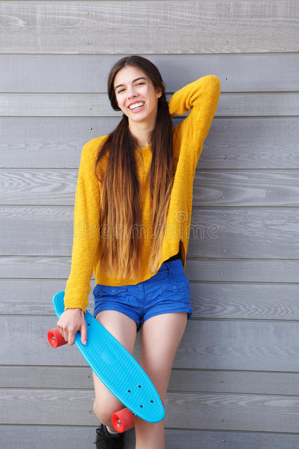 Smiling young woman leaning against wall with skateboard royalty free stock photo