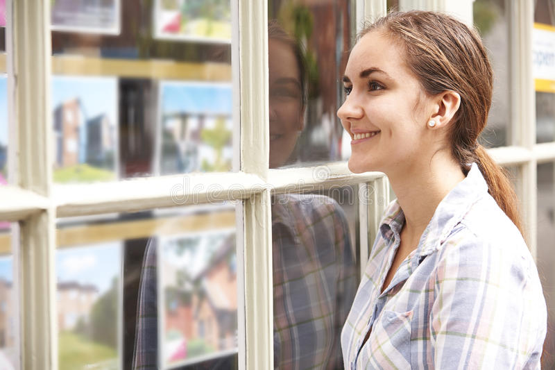 Smiling Young Woman Looking In Window Of Estate Agents. Young Woman Looking In Window Of Estate Agents royalty free stock photo