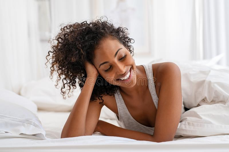 Smiling young woman lying on bed royalty free stock photo