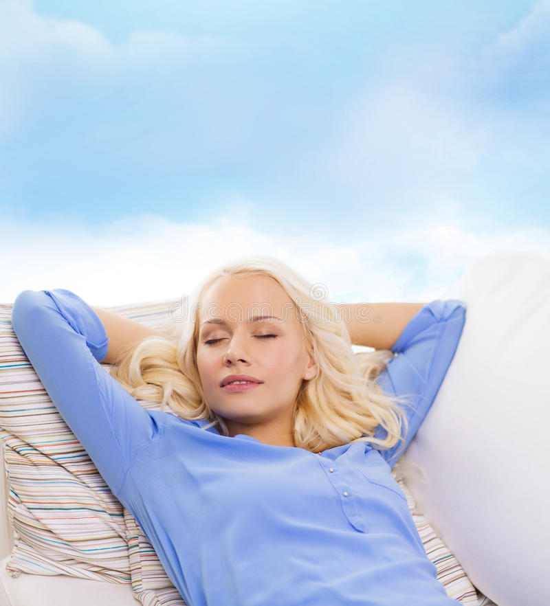 Smiling young woman lying on sofa royalty free stock photos