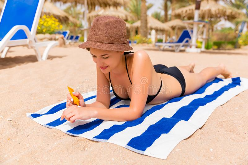 Smiling young woman is lying on striped towel on the sand at the beach and applying sun cream on her hand royalty free stock photos
