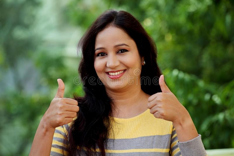 Smiling young woman making thumb up gesture at outdoors royalty free stock images