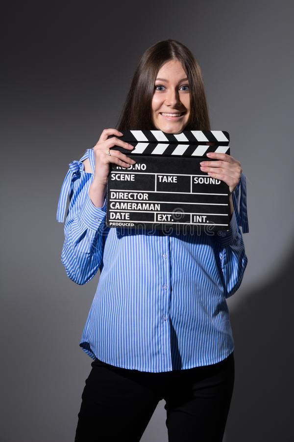 Smiling young woman with movie clapper. Assistant director girl with long hair and striped shirt on a gray background stock images