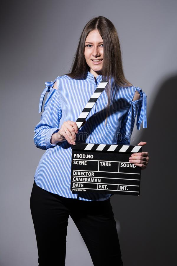Smiling young woman with movie clapper. Assistant director girl with long hair and striped shirt on a gray background stock photos