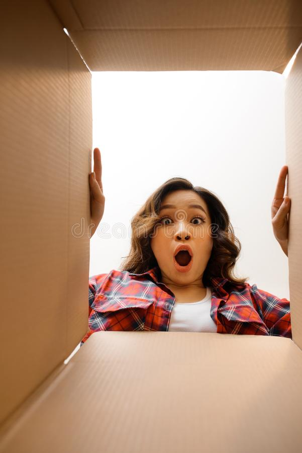 Smiling young woman opening a carton box, relocation and unpacking concept royalty free stock image