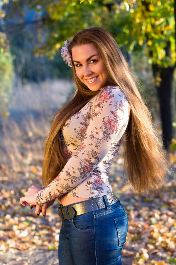 Smiling young woman outdoors. Portrait of a smiling young woman outdoors stock image