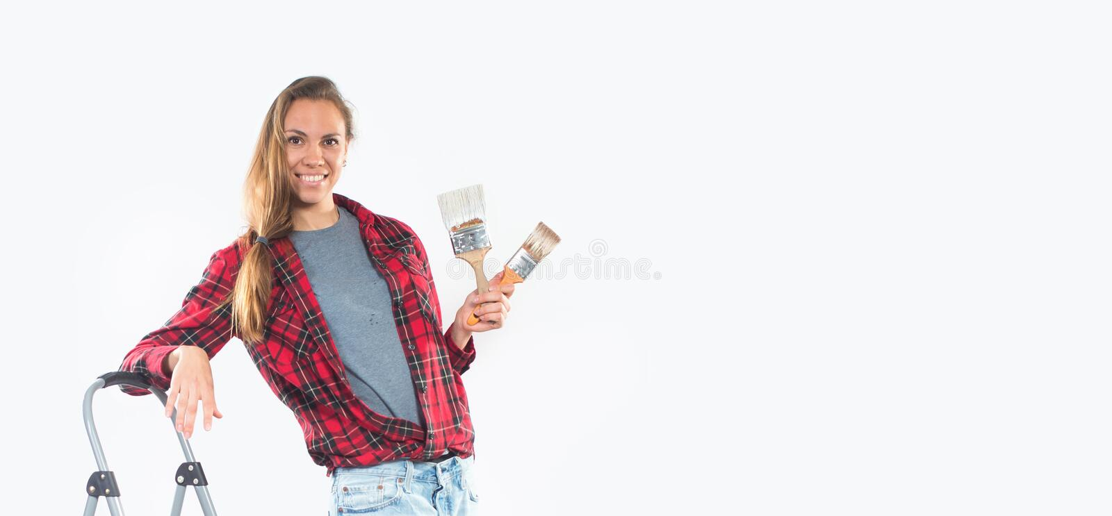 Smiling young woman with paintbrushes near empty wall stock photography