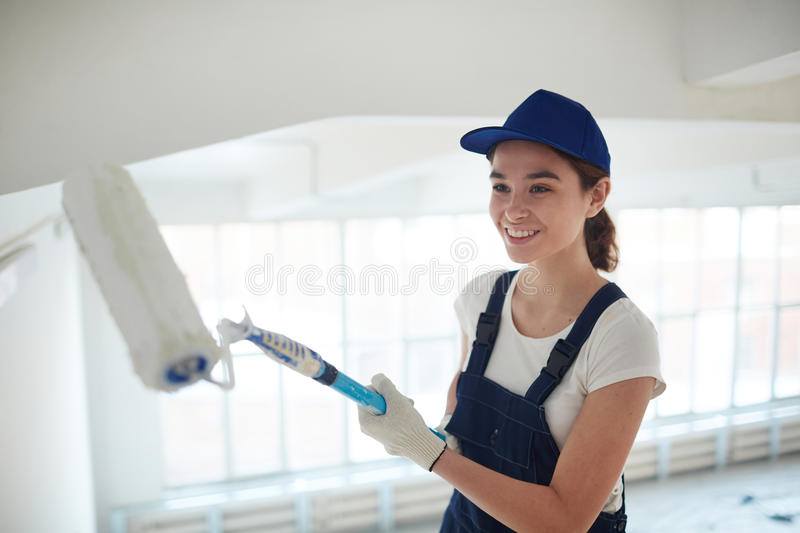 Smiling Young Woman Painting Walls royalty free stock image