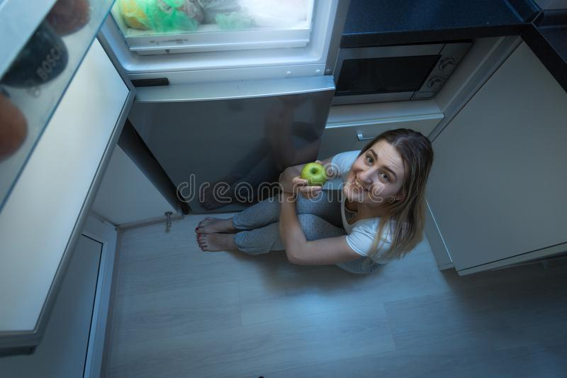Portrait of smiling young woman in pajamas sitting on kitchen floor at night and holding taste fresh green apple royalty free stock image