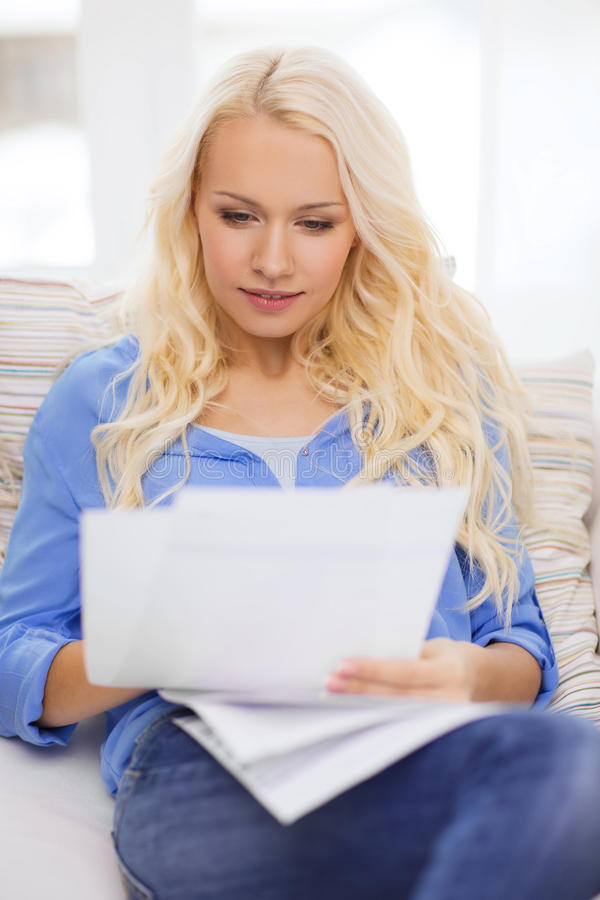 Smiling young woman with papers at home. Tax, finances, home and happiness concept - smiling young woman with papers at home stock photography