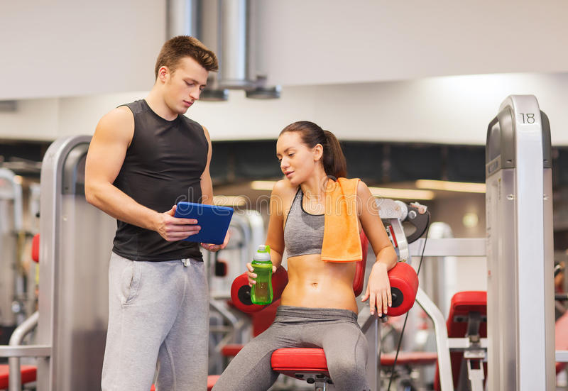 Smiling young woman with personal trainer in gym royalty free stock photography