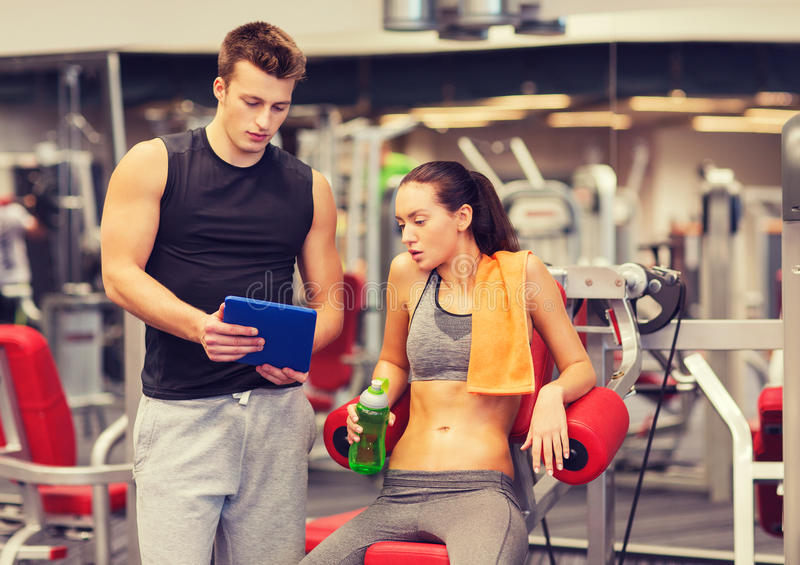 Smiling young woman with personal trainer in gym stock photo
