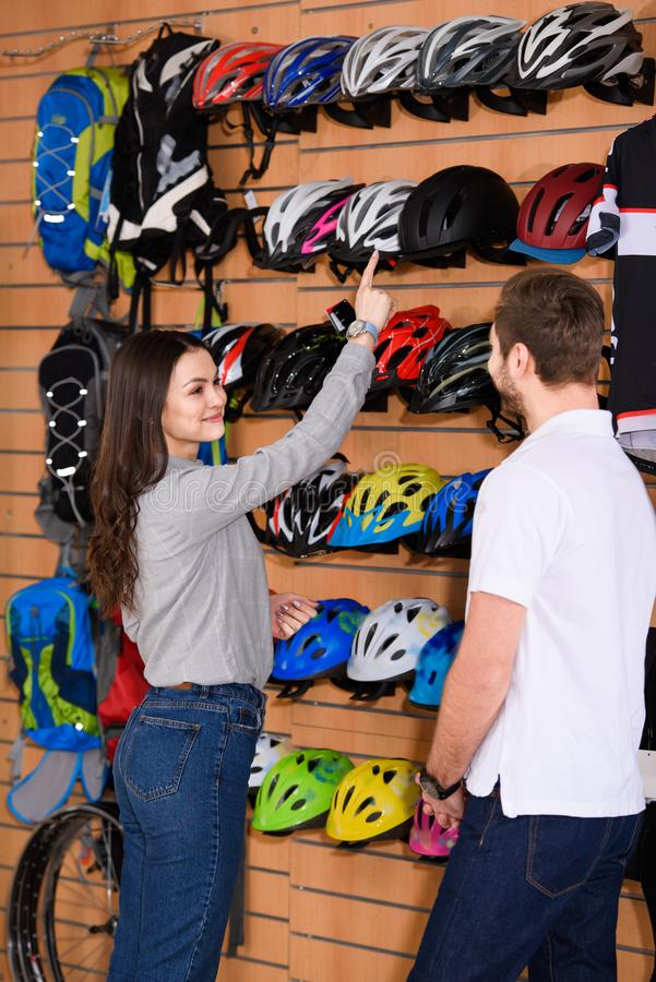smiling young woman pointing with finger at bicycle helmet and looking at seller royalty free stock images