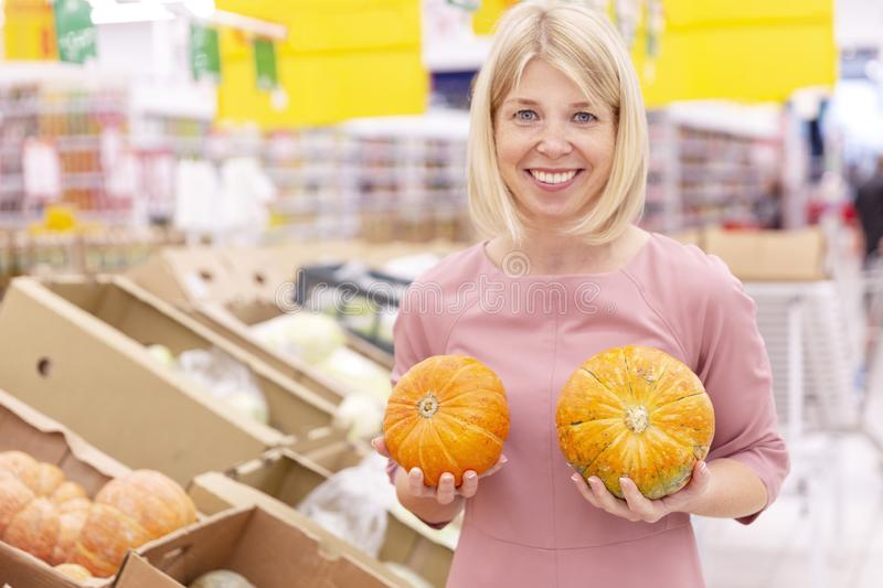 Smiling young woman with pumpkins in hands in a hypermarket. Humor and positive. Iling young woman with pumpkins in hands in a hypermarket. Humor and positive stock photo