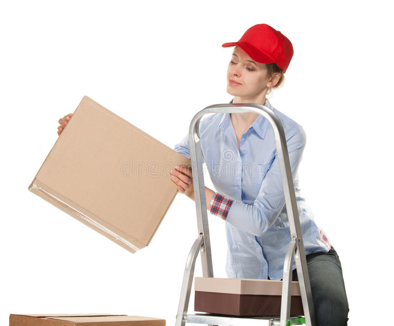 Smiling young woman puts a box stock images
