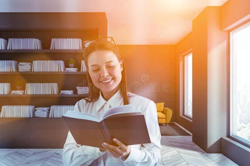 Smiling young woman reading book in home library stock photography