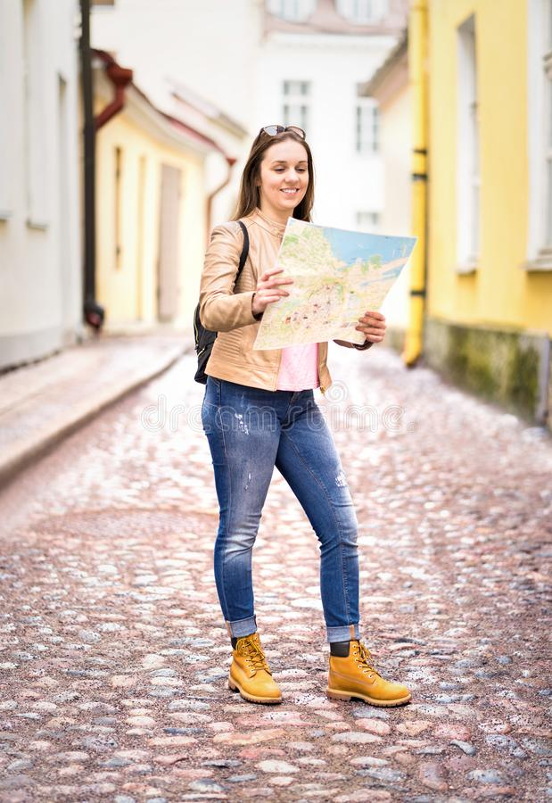 Smiling young woman reading map. Vertical shot of happy traveler. With backpack navigating and planning sightseeing tour in city. Travel and tourism concept royalty free stock photos