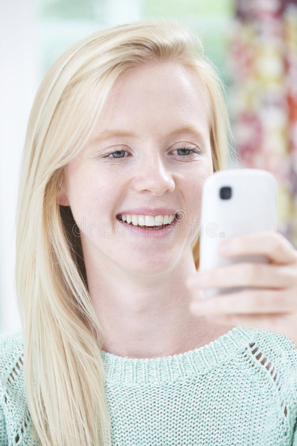 Smiling Young Woman Reading Text Message. Young Woman Reading Text Message royalty free stock images
