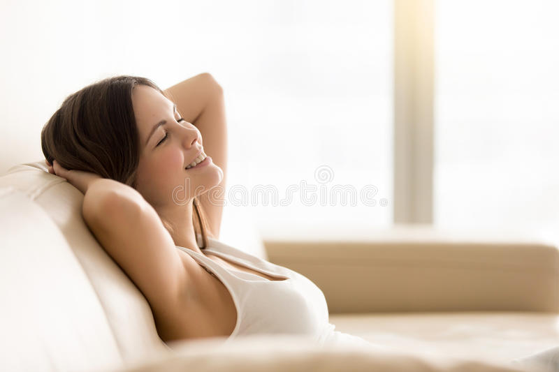 Smiling young woman relaxing on coach at home royalty free stock image